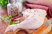 stock photo of gobbler  - raw chicken leg with spice on the board