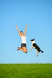 pic of working-dogs  - Joyful sporty woman and dog jumping and having fun after running and exercising outdoor together - JPG