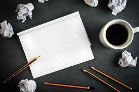 stock photo of storyboard  - Creative Writing Concept With Pencils Coffee Cup Notepad and Crumpled Paper on Table Top View - JPG
