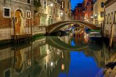 stock photo of dock  - Lateral canal and pedestrian bridge in Venice at night with street light illuminating bridge and houses - JPG