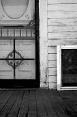 stock photo of screen-porch  - Black and white image of old screen door and porch - JPG
