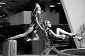 image of trolley  - Two alluring fashionable girls in dresses with shopping trolley indoor on shop background black and white horizontal picture