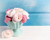 stock photo of blue rose  - Pastel roses in turquoise vase on white wooden background against blue wall - JPG