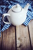 image of teapot  - Large white porcelain teapot and a blue linen napkin on old wooden board, rustic kitchen background. ** Note: Soft Focus at 100%, best at smaller sizes - JPG