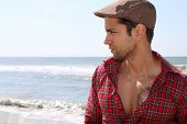 stock photo of beret  - handsome man wearing a beret next to the sea - JPG