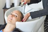 stock photo of wash-basin  - Young woman at the hairdressing salon having her hair washed and shampooed at a basin by the stylist prior to cutting smiling at the camera - JPG