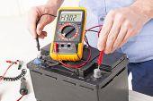 stock photo of  multimeter  - Testing car battery with digital multimeter - JPG