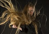 stock photo of hair blowing  - Mysterious Looking Blond Woman Wearing Black Dress Standing in Studio with Black Background with Long Hair Blowing in Strong Wind - JPG