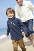 pic of grandfather  - Grandfather And Grandson Running Along Beach - JPG