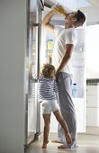 stock photo of raid  - Father And Son Raiding The Fridge For Drink - JPG