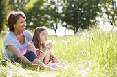 picture of granddaughter  - Grandmother And Granddaughter Sitting In Summer Field - JPG