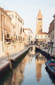image of tilt  - Tilt shift photo of Venice street with boat and tower - JPG