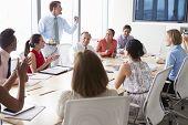 stock photo of motivation talk  - Motivational Speaker Talking To Businesspeople In Boardroom - JPG