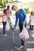 stock photo of pick up  - Family Picking Up Litter In Suburban Street - JPG