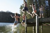 foto of jetties  - Group Of Young People Jumping From Jetty Into Lake - JPG