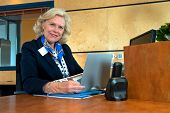 pic of receptionist  - Smiling senior receptionist sitting at the front desk as an example of successful reintegration after retirement - JPG