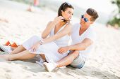 pic of couple sitting beach  - Young couple sitting on a sandy beach - JPG
