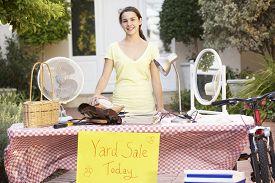 picture of yard sale  - Teenage Girl Holding Yard Sale - JPG