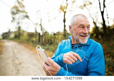 poster of Senior runner in nature. Man with smart phone with earphones. Listening music or using a fitness app. Using phone app for tracking weight loss progress, running goal or summary of his run.