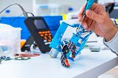 Robotics development closeup. Electronics engineer or programmer hands with special tools working wi poster