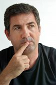 Mature Man Thinking With One Finger On His Lips Looking Away. poster