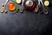 Tea cup and assortment of dry tea in spoons on stone table. Top view with copy space poster