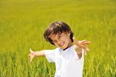 stock photo of happy kids  - Happy kid on green field with widely opened arms - JPG