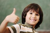 Happy boy in classroom with thumb up: green board behind