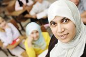 stock photo of tweenie  - Muslim female teacher in classroom with children pupils  - JPG