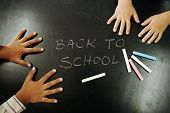 Multiraces children hands on blackboard with chalks: back to school!