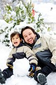 stock photo of winter scene  - Father and son playing happily in snow making snowman - JPG