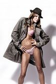 sexy woman in pink underwear and topcoat with hat, studio white