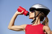 young woman drinking water after doing some bicycle exercise