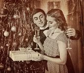 Retro vintage portrait of couple on party near Christmas tree. Couple drink champagne. Girl keep gif poster