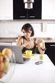 Постер, плакат: женщина работающая с ее ноутбуком во время еды ее завтрак выборочный фокус с мелкой DOF
