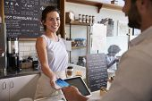 Customer at coffee shop pays smiling waitress with card poster