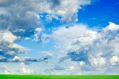 White fluffy clouds and a green spring field. poster