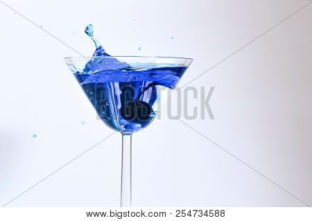 poster of Cocktail With Blue Liquid In Glass. Glass With Blue Water Pouring With Liquid With Splashes And Drop