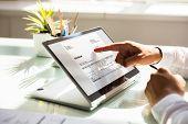 Businessman Examining Invoice On Laptop poster