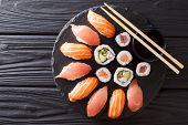 Sushi Rolls Set Served On Black Stone Slate On Dark Background. Horizontal Top View poster