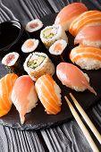Постер, плакат: Served A Set Of Sushi With Salmon And Tuna California Rolls Maki Soy Sauce Closeup On The Table