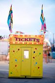 A Carnival Ticket Booth And Rides. Bright Lights And Saturated Colors Beckon Crowds To The Carnival. poster