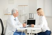 Male doctor consulting patient in clinic poster