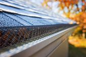 Plastic guard over gutter on a roof, shallow focus on mesh poster