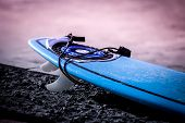 New Surfboard On The Coastline At Sunrise On The Ocean. Blue Surf Board Laying On The Coastline Wait poster