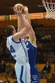 KAPOSVAR, HUNGARY - OCTOBER 15: Jozsef Lekli (in white) in action at a Hugarian National Championship basketball game Kaposvar (white) vs. Jaszbereny (blue) on October 15, 2011 in Kaposvar, Hungary.