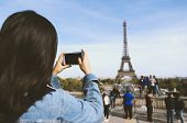 Woman Tourist Taking Photo By Phone Near The Eiffel Tower In Paris Under Sunlight And Blue Sky. Famo poster