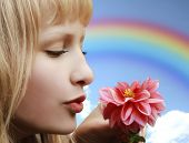 Beautiful girl with flower on rainbow background