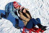 Portrait of happy couple tobogganing in winter