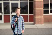 Candid portrait of a male elementary school student standing outside the school building. Handsome b poster